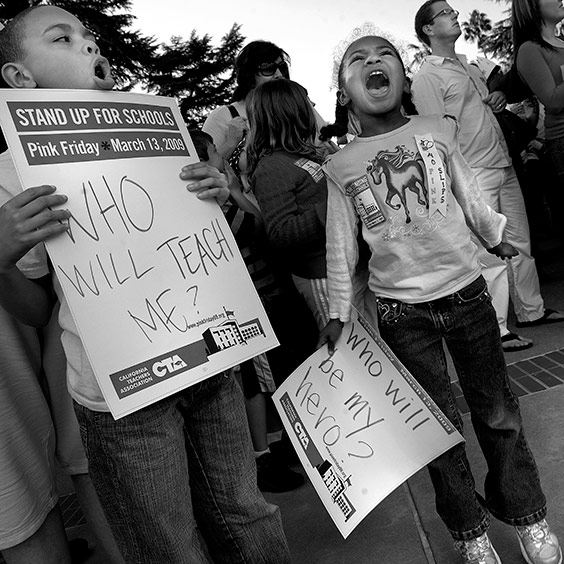 Third grader Devin Bryson, 8, and kindergartener Elizabeth Bryson, 6, both students at Matusuyama Elementary School, shout in support of teachers at the State Capitol in Sacramento, California, on Friday March 13, 2009. Public school teachers gathered outside the Capitol—after school hours—to protest the estimated 25,000 preliminary layoffs of teachers, librarians and other staff statewide due to cuts in education funding. Many demonstrators dressed in pink to call attention to the pink slips. The California Teachers Association blasted the unusually high number of cuts as school districts tinkered with their budgets in hopes of limiting layoffs.