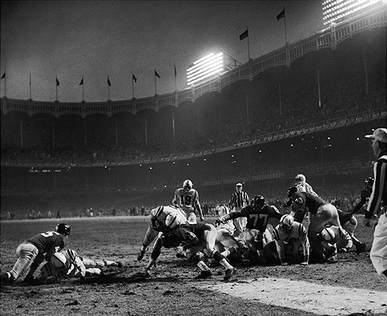 "Yankee Stadium, Bronx, NY, December 28, 1958  In 1958, I started going to Yankee Stadium every Sunday for Giants home games. I couldn't afford a ticket, but I discovered that about an hour before game time, buses from a veterans' hospital pulled up outside the stadium with forty or fifty veterans in wheelchairs. They always needed people to help wheel the veterans into the stadium. I volunteered, quickly becoming a regular. We would position the wheelchairs up against the center field wall, a few feet behind the end zone. Under my coat, I always had my Yashica-Mat camera. On my sixteenth birthday, December 28, 1958, I found myself standing ten yards directly in front of Alan Ameche as he scored the winning touchdown in that famous ""Sudden Death"" game. What a wonderful birthday present! -- A picture that even today, fifty-one years later, is unquestionably one of my very best."