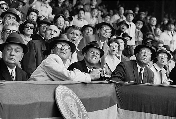 Griffith Stadium, Washington, DC, April 10, 1961  I was eighteen years old and the idea of sitting twenty feet in front of the President was more thrilling than shooting any baseball game could ever be. Unfortunately, by the third or fourth inning, it was clear that I hadn't yet gotten any memorable pictures. I'd hoped that Kennedy would do something to make a good picture. He might eat a hot dog and end up with a little mustard on his lip. Johnson ate one, but he wasn't the subject I was there to shoot. Kennedy didn't order a dog, but he donned a fedora – which was not a bad picture. Finally, I got lucky when a foul ball came dangerously close to the presidential box, causing the President, Vice President, and Democratic and Republican leaders from both houses of Congress to all lean to the left. Surely it was the most bipartisan moment of 1961.