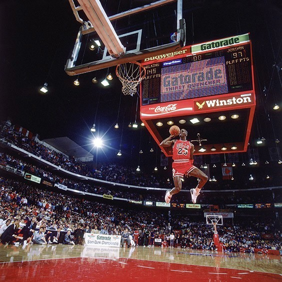 "Chicago, IL, 1998  The problem with shooting the NBA slam-dunk contest was that you never knew how the players were going to dunk, especially Jordan. As he sat in the stands three hours before the contest, I said, ""Michael, can you tell me which way you're going to go, so I can move and get your face in the picture?"" He looked at me as if I were crazy but then said, ""Sure. Before I go out to dunk I'll put my index finger on my knee and point which way I'm going."" So later, when they announced his name, I looked over to him on the bench and there was his finger pointing left."
