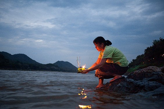 "Laos, 2009  A woman launches an offering on the Mekong River, known to Laotians as the ""mother of waters."" The occasion is Boun Pi Mai Lao, the New Year's celebration, in April."