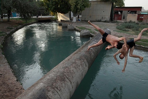 Tajikistan, 2009  Launching themselves off a drainage pipe, young men in a village in southwestern Tajikistan cool off in the only swimming hole around: an irrigation canal.
