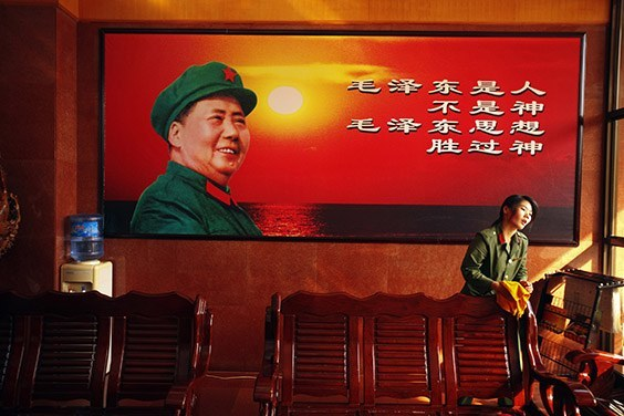 A hotel staff member polishes benches under a picture of Chairman Mao Zedong on November 3, 2009 in Nanjie village, Henan province, China. Nanjie is a model collective village run along Maoist lines. Residents live in identical apartments and receive free health care and education, but earn only a token salary, paid in coupons rather than currency. The government-supported Red Tourism program glorifies the deeds of past communist leaders through monuments, battle reenactments and tours of model communist villages like Nanjie. Hardly a reference can be found to the millions killed during the Great Leap Forward and the Cultural Revolution.
