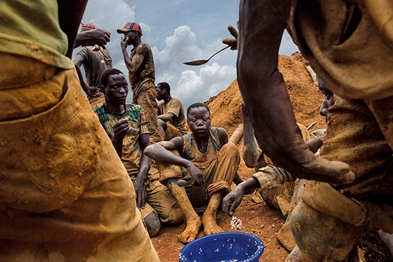 Pluto, Democratic Republic of the Congo, 2013 Miners eat lunch from a communal bowl in the mining town of Pluto in Ituri Province. They work here to extract rock and sand from a large pit that has taken over a year to excavate. The miners are made up of many different people from all over Congo who come to seek their fortune.