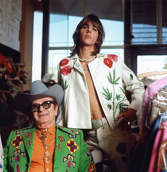 Gram Parsons (standing), adopting the rhinestone look of his country music heroes, in a personalized suit designed by Nashville's favorite tailor, Nudie Cohn (seated), at Nudie's Rodeo Tailors shop, Los Angeles, 1968