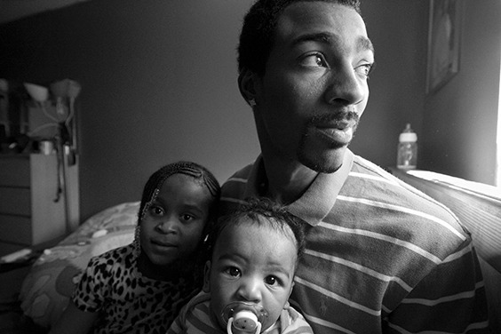 "Guy Miller relaxes in his bedroom with oldest daughter Nijeyah and newborn son Guy ""Chum"" Jr. Bronx, NY, USA. October 2012. Portrait from the series Father Figure: Exploring Alternate Notions of Black Fatherhood."