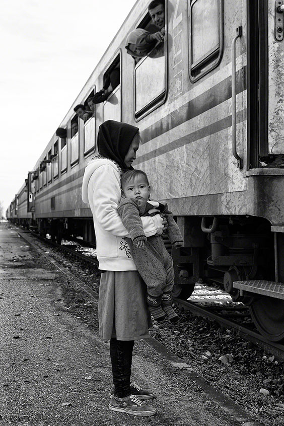 A mother carries her daughter across the border between Serbia and Croatia.