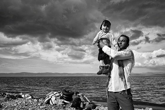 A father celebrates his family's safe passage to Lesbos after a stormy crossing over the Aegean Sea from Turkey.